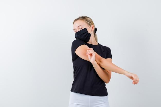 Retrato de jovem esticando o braço em camiseta, calça, máscara médica e parecendo com sono