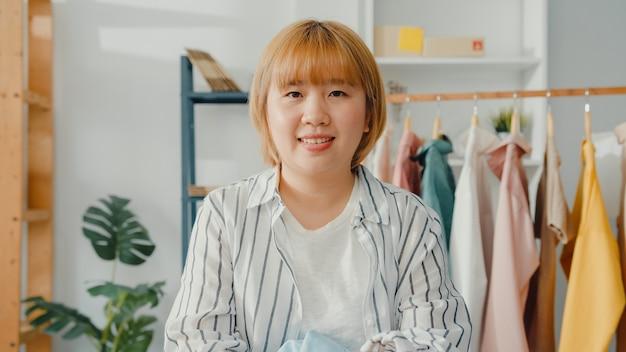 Retrato de jovem estilista asiática com sorriso feliz, braços cruzados e olhando para frente enquanto trabalhava na loja de roupas no escritório em casa