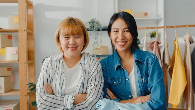 Retrato de jovem estilista de mulheres asiáticas com sorriso feliz, braços cruzados e olhando para frente enquanto trabalhava na loja de roupas no escritório em casa