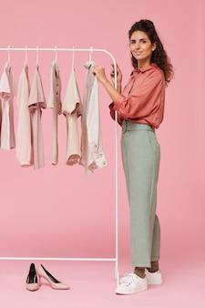 Retrato de jovem estilista em pé perto do cabide com roupas e sorrindo isolado no fundo rosa