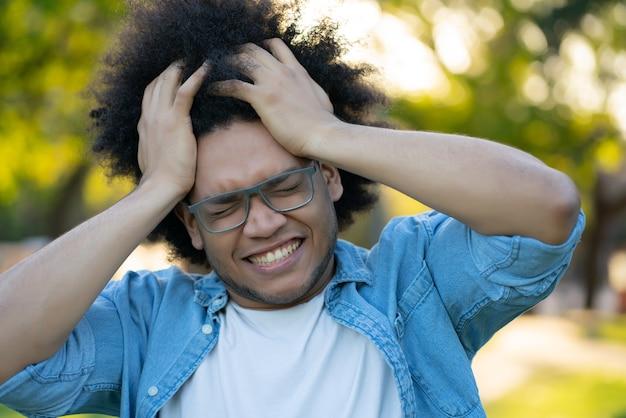 Retrato de jovem estressado, sofrendo de dor de cabeça ao ar livre na rua.