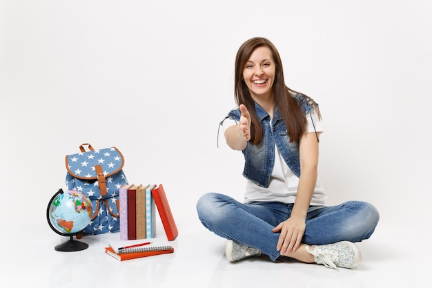 Retrato de jovem estudante casual sorridente, sentado com a mão estendida para saudar perto do globo, mochila, livros escolares isolados
