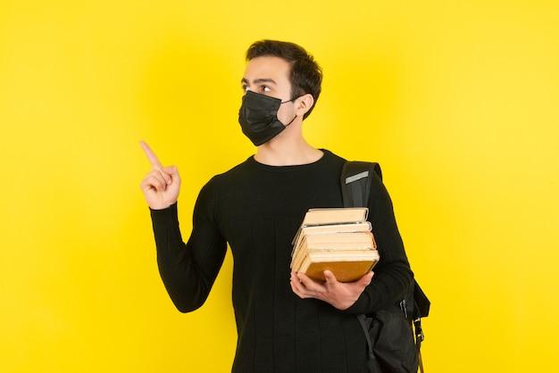 Retrato de jovem estudante com máscara médica, segurando livros da faculdade e apontando