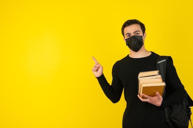 Retrato de jovem estudante com máscara médica, segurando livros da faculdade e apontando Foto Premium