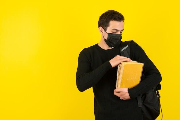 Retrato de jovem estudante com máscara médica segurando livros universitários na parede amarela