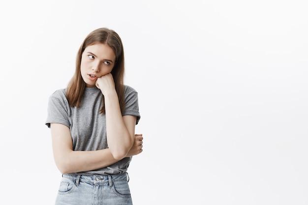Retrato de jovem estudante infeliz linda garota com cabelos escuros na roupa casual, olhando de lado com expressão cansada, segurando a cabeça com a mão, sendo chateado palestra chata.
