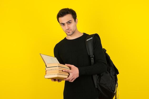 Retrato de jovem estudante lendo livros sobre a parede amarela