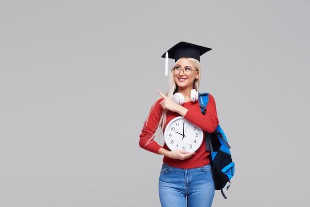 Retrato de jovem estudante loira animado na tampa de pós-graduação com mochila segurando o despertador grande isolado no espaço cinza. educação na faculdade. copie o espaço para texto