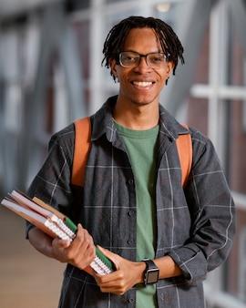 Retrato de jovem estudante segurando um monte de cadernos