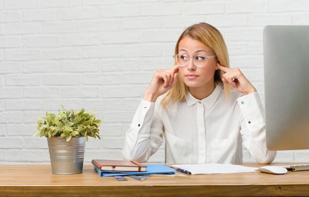 Retrato, de, jovem, estudante, sentando, ligado, dela, escrivaninha, fazendo, tarefas, cobertura, orelhas, com, mãos
