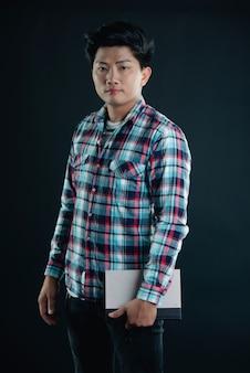 Retrato de jovem estudante universitário com livros a sorrir