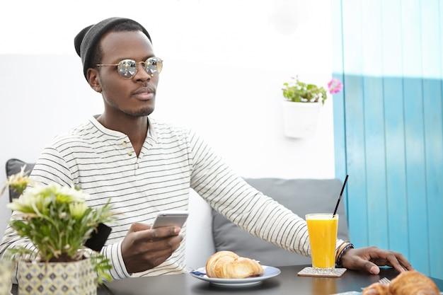 Retrato de jovem europeu elegante bonito preto tomando café da manhã no café, sentado à mesa com suco de laranja fresco e croissant, usando a conexão de internet sem fio em seu dispositivo eletrônico