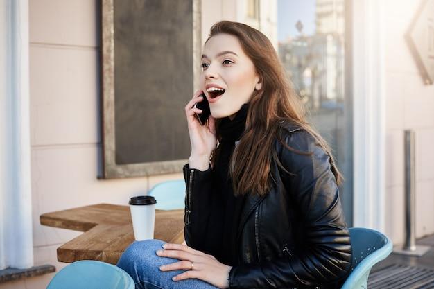 Retrato de jovem europeu feminino impressionado e animado com roupa elegante, sentado no café, tomando café e falando no smartphone