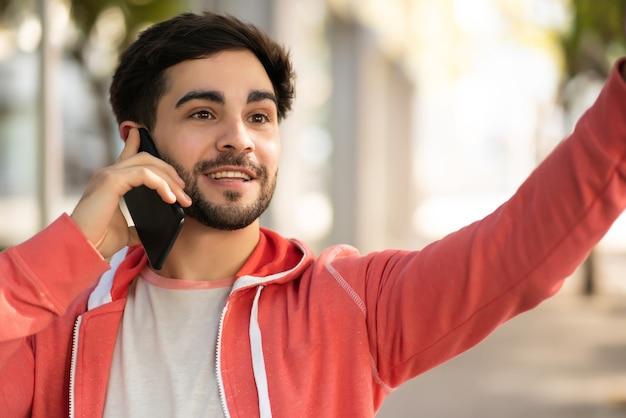 Retrato de jovem falando ao telefone e levantando a mão para chamar um táxi em pé ao ar livre na rua. conceito urbano.