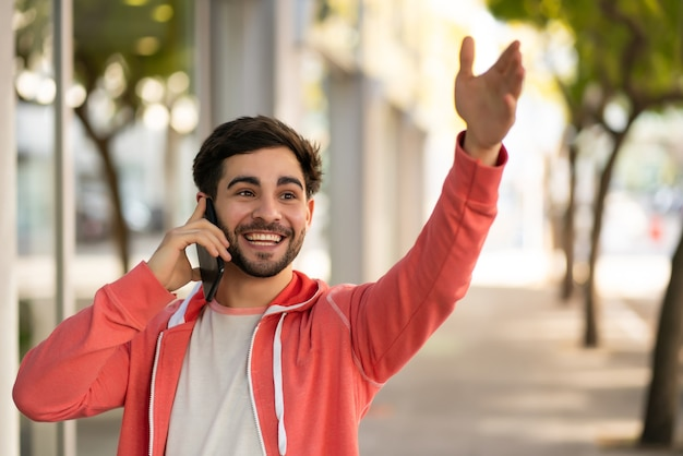 Retrato de jovem falando ao telefone e levantando a mão para chamar um táxi em pé ao ar livre na rua