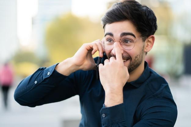Retrato de jovem falando ao telefone em pé ao ar livre na rua. conceito urbano.