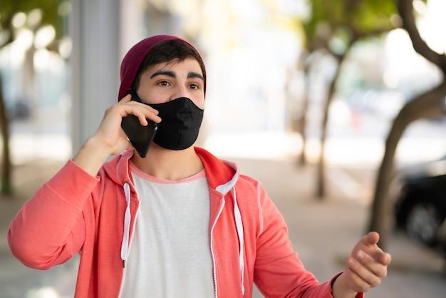Retrato de jovem falando ao telefone enquanto caminha ao ar livre na rua. homem usando máscara facial. conceito urbano.