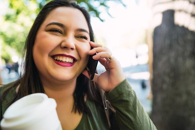 Retrato de jovem falando ao telefone enquanto segura uma xícara de café ao ar livre na rua