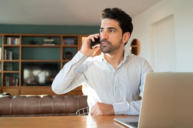 Retrato de jovem falando em seu telefone celular e trabalhando em casa com o laptop. conceito de escritório em casa.