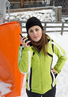 Retrato de jovem falando no rádio em uma pista de esqui