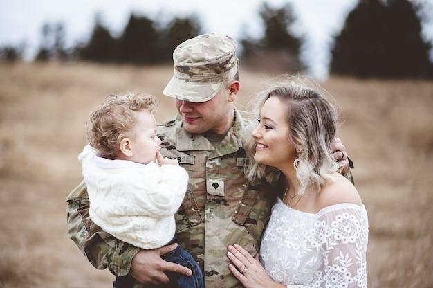 Retrato de jovem família - um pai soldado segurando seu filho e uma bela jovem esposa