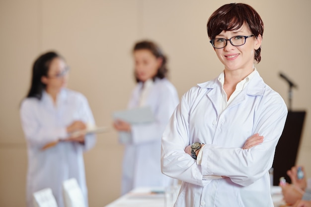 Retrato de jovem farmacologista confiante usando óculos, cruzando os braços e olhando para a câmera