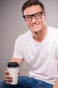 Retrato de jovem feliz bebendo café.