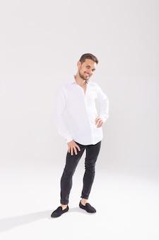 Retrato de jovem feliz bonito na camisa casual em pé contra um fundo branco.