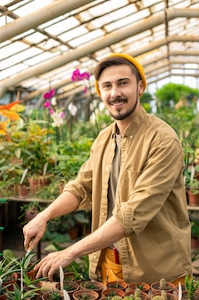 Retrato de jovem feliz com chapéu em pé no balcão com plantas jovens em vasos e plantando jardim em estufa