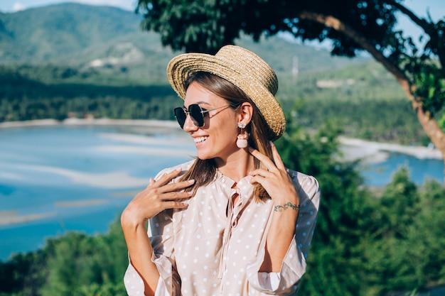 Retrato de jovem feliz com vestido de verão, óculos escuros e chapéu de palha
