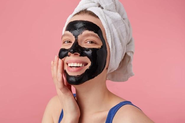 Retrato de jovem feliz depois do banho com uma toalha na cabeça, com máscara preta, toca o rosto e sorri, fica de pé.
