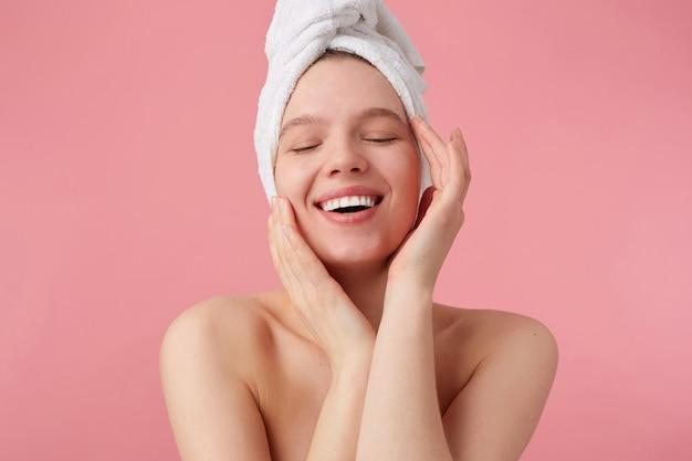 Retrato de jovem feliz depois do banho com uma toalha na cabeça, sorri amplamente com os olhos fechados, toca o rosto e a pele lisa, fica de pé