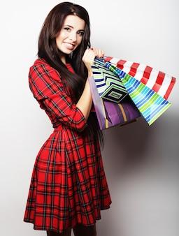 Retrato de jovem feliz e sorridente com sacolas de compras, sobre fundo branco
