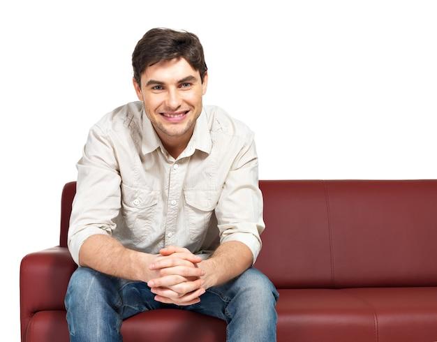 Retrato de jovem feliz e sorridente se senta no divã, isolado no branco.