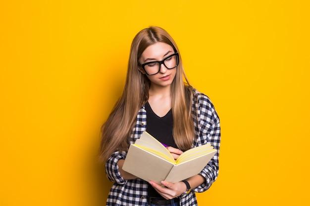 Retrato de jovem feliz lendo livro de educação, estudando aprendizagem, conhecimento e sorrindo emoção positiva na parede amarela