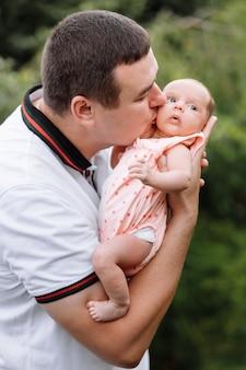 Retrato de jovem feliz segurando e beijando seu lindo bebê recém-nascido ao ar livre