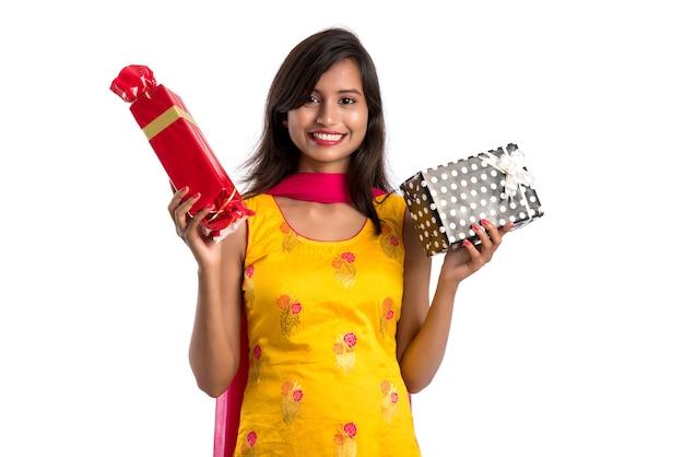 Retrato de jovem feliz sorridente indiana segurando caixas de presente em um branco.