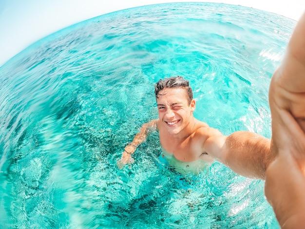 Retrato de jovem feliz tirando uma selfie na praia em uma água azul turquesa se divertindo e curtindo as férias sozinho ao ar livre.
