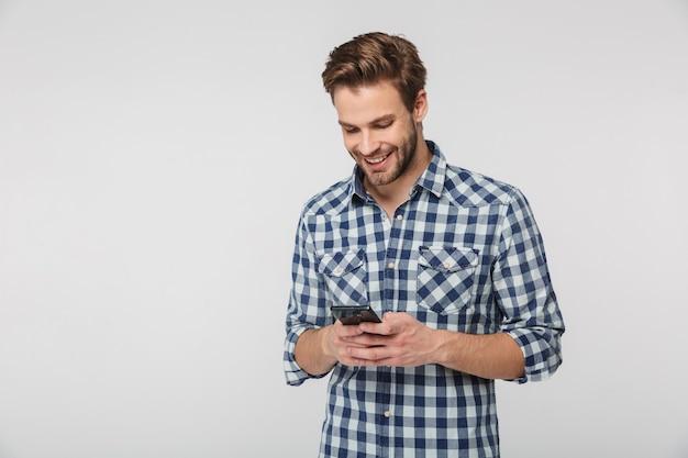 Retrato de jovem feliz vestindo camisa xadrez, sorrindo e usando celular isolado na parede branca