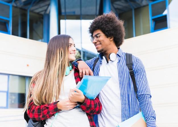 Retrato, de, jovem, femininas, e, estudante masculino, ficar, exterior, a, campus, olhando um ao outro