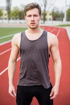 Retrato de jovem fitness em pé na pista de campo