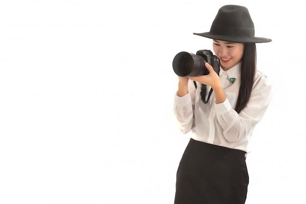 Retrato de jovem fotógrafo asiático de chapéu preto tirando uma foto