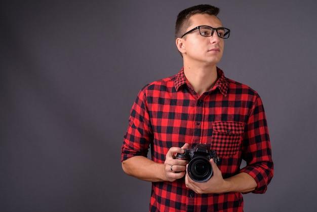 Retrato de jovem fotógrafo segurando uma câmera