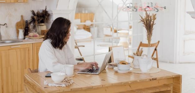 Retrato de jovem freelancer caucasiana de sucesso sentado na mesa em casa mulher confiante trabalhando on-line no laptop em casa