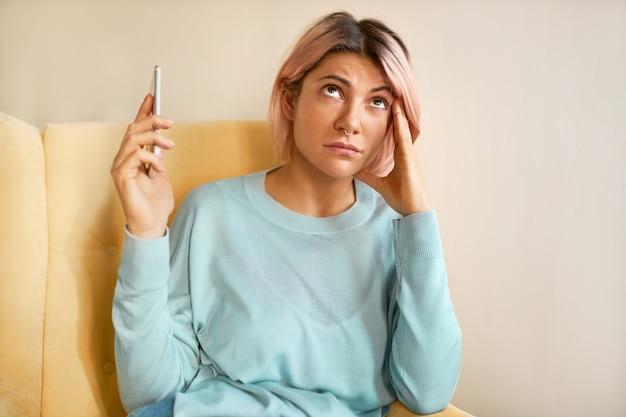 Retrato de jovem freelancer frustrada com cabelo rosado e dor de cabeça, segurando a mão na têmpora enquanto falava com uma cliente descontente, movendo o telefone para o lado para não ouvir gritos do outro lado