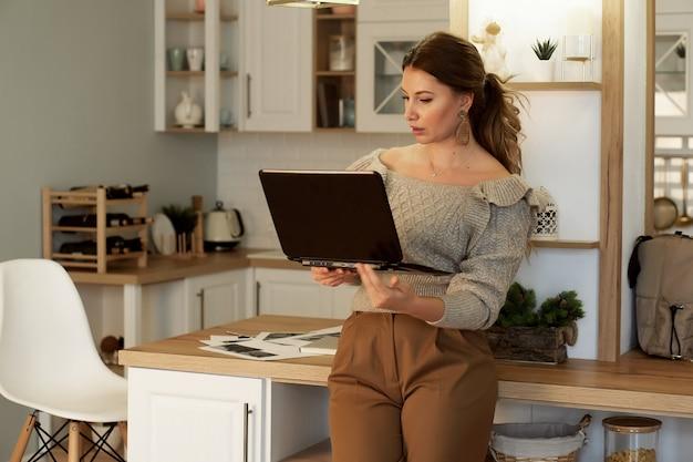 Retrato de jovem freelancer trabalhando em casa em um laptop