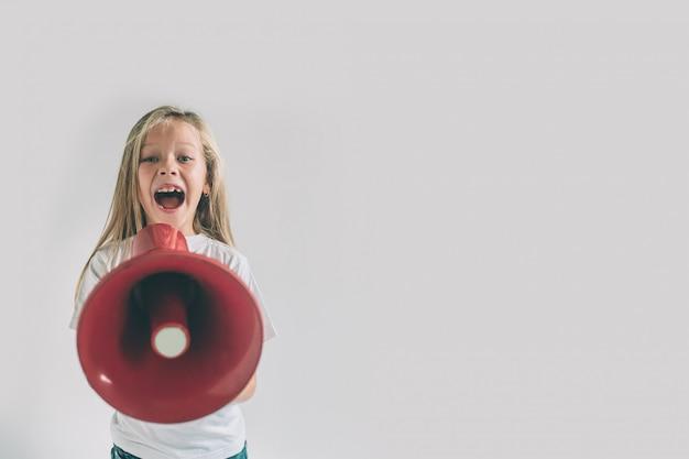 Retrato de jovem garota gritando usando o megafone