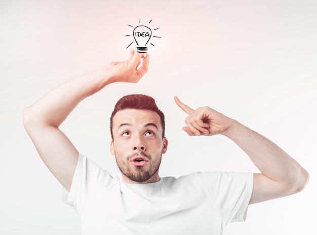 Retrato de jovem gênio segurando a lâmpada. cara com uma ideia