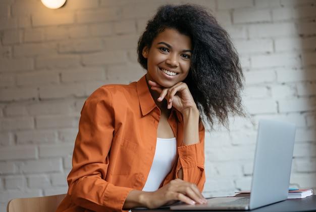Retrato de jovem gerente de sucesso sentado no escritório