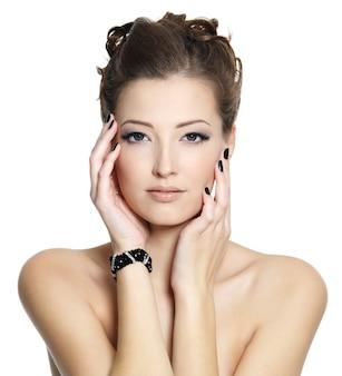 Retrato de jovem glamour com unhas pretas e maquiagem nos olhos, posando em branco